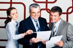 Portrait of happy businessmen looking into document at which elegant lady pointi Stock Photos