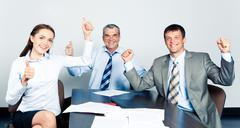 Team of three office workers showing a successful sign Stock Photos