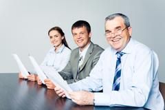 Ryhmä menestyksekkäitä liikemiehiä istuu pöydässä vanhempi johtaja f Kuvituskuvat