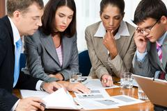 photo of business group sitting at the table and watching at documents on it wit - stock photo