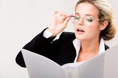 Portrait of smart businesswoman in glasses looking at document in her hand and r Stock Photos