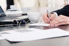 Hands of businesswoman writing something on paper with laptop, cup, pen and docu Stock Photos