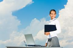 Portrait of attractive business lady holding folder on the background of sky Stock Photos