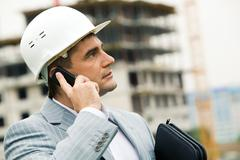photo of confident contractor wearing helmet with mobile phone looking upwards - stock photo