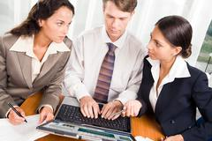 Image of two serious women looking at each other with businessman sitting betwee Stock Photos