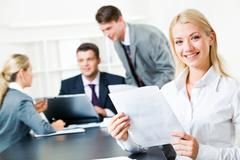 portrait of white collar worker holding document on the background of her collea - stock photo