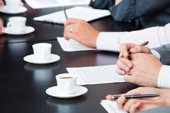 image of businesspeople's hands with pens, papers and cups of coffee near by - stock photo