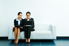 Portrait of business ladies sitting next to one another on the sofa and looking Stock Photos