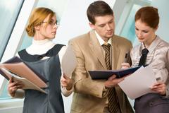 Portrait of confident associates looking at business document and reading it bef Stock Photos