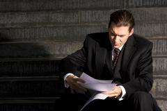 Portrait of unhappy businessman reading the document Stock Photos