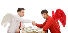Image of deal between god and devil over table with dollars Stock Photos