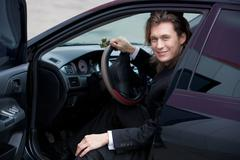 portrait of cheerful ceo looking out of his automobile and looking at camera wit - stock photo
