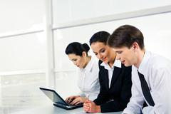 Portrait of two businesspartners communicating while looking at document with bu Stock Photos