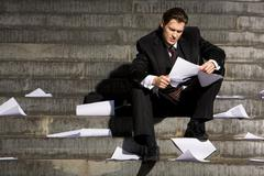Portrait of depressed employee sitting in frustration on stairs with papers in h Stock Photos