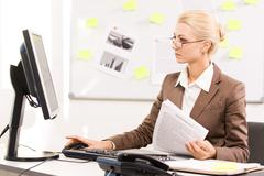pretty specialist looking at monitor of computer while sitting in office - stock photo