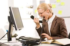 Photo of aggressive secretary shouting into phone receiver while sitting in offi Stock Photos