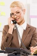 Portrait of helpful secretary speaking on the phone with a client Stock Photos