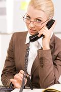 portrait of smart agent speaking by telephone - stock photo