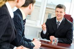 Confident boss proposes new terms of transaction to business partners at meeting Stock Photos