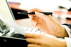 Businesswoman' holding a pen and a document Stock Photos