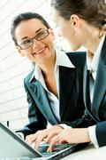 Portrait of business woman with glasses gazing at her colleague and smiling Stock Photos