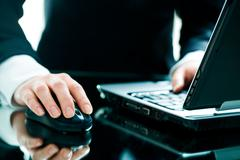 image of businesswoman's hand on the mouse with a laptop near by - stock photo