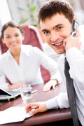 Business man calling on cellphone while conversation with colleague Stock Photos