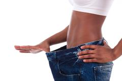 young african woman in old jeans pant after losing weight - stock photo
