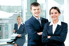 Portrait of two business people folding one's arms in the office Stock Photos