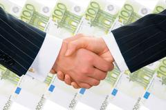 Creative photo of businesspeople handshake on the background of hundred euro ban Stock Photos