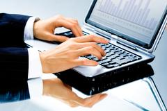 Image of human hand typing a business document on the laptop Stock Photos