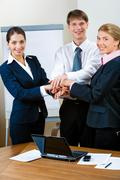 image of three standing business partners making a pile with their hands and loo - stock photo