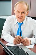 Portrait of boss sitting at the table with document and laptop on it Stock Photos