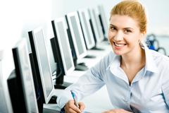 Portrait of student or teacher sitting at the computer table in front of monitor Stock Photos