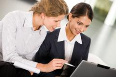 Portrait of two smiling business women working together Stock Photos