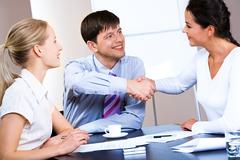 portrait of woman and man concluding a bargain at business meeting - stock photo