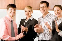 Muotokuva neljä liikemiehet hymyilee ja taputtaa toimistossa Kuvituskuvat