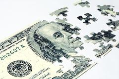 image of dollar made of puzzles over white background - stock photo