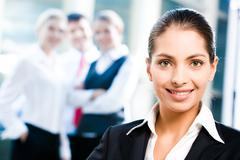 face of female leader on the background of her business team - stock photo