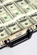 close-up of briefcase with plenty of us dollars in it - stock photo