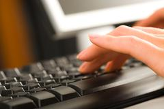 a secretary typing business documents on the computer - stock photo