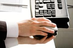 image of hand with computer mouse placed on a working table - stock photo