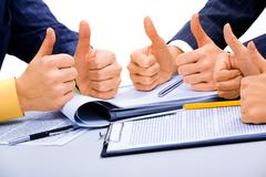 Success in business: people giving the thumbs-up sign Stock Photos