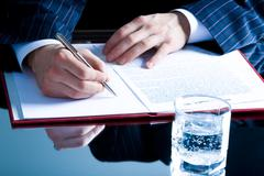 Image of human hand holding a pen over paperwork Stock Photos