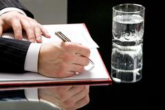 Stock Photo of view of human hands on with a pen ready to write with a glass of water standing