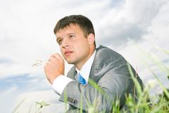 close-up of pensive businessman with blade in his mouth looking somewhere with s - stock photo