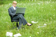 Photo of pretty specialist sitting in armchair on green grass with laptop and wo Stock Photos