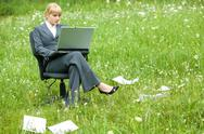 Stock Photo of photo of pretty specialist sitting in armchair on green grass with laptop and wo