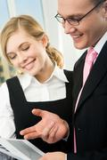 vertical image of confident man pointing at paper while pretty businesswoman loo - stock photo