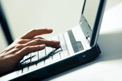 close-up of businesswoman's fingers pushing keys of laptop on desk - stock photo
